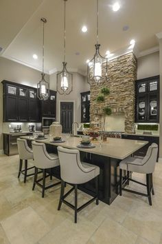 Giant pendant lighting, dark cabinets, comfy chairs, stacked stone range hood. Very unique.