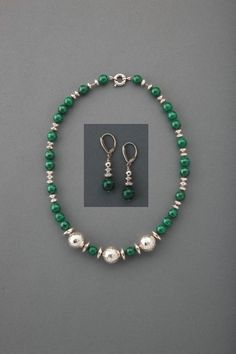 Magnificent Malachite Necklace . . . The wearing of the green with fabulous round Malachite Gemstones. Exciting your eye are three Hill Tribe Silver Beads placed harmoniously and surrounded with numerous Sterling Silver. Closure is a Sterling Silver Ring Clasp. Limited Edition. L 17 . . . . . . . . . . . . Paired with Malachite Happiness Earrings. . . Malachite Gemstones designed with Sterling Silver beads on Sterling Silver Shield Lever Backs.