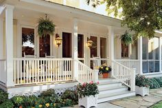 Add charm with hanging ferns—a quintessential feature for any Southern porch. Cheery containers also add inviting color to this porch. See more Porches and Patios