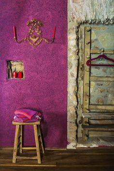 Vestidor rústico y colorido en fucsia brillante, piedra y madera. Parte del Château Castigno, en la región francesa de Languedoc-Rosellón.