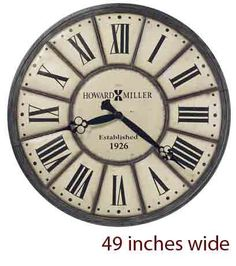 """This massive iron wall clock is 49"""" in diameter and is finished in off-white with an antique nickel outer ring that is moderately distressed and dented for an aged appearance. Black Roman numerals are centered on individual antique off-white panels. Quartz, battery-operated movement requires one AA sized battery. Some assembly is required. One year warranty and Free ..."""