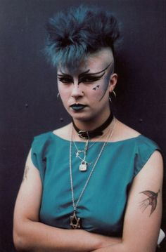 gorgonetta:  [A color photo of a woman with incredibly ornate eyeliner, a black line under her cheekbone, teal lipstick, and a teal mohawk.  She wears several simple silver necklaces and a black dog collar, and has a tattoo of a bird (?) on her left arm, and wears a sleeveless teal shirt.] I like how early (I'd guess this is a pic from the 80s or 90s?) punks and goths didn't go so over the top as one is practically obligated to do now in order to belong.  By the early 90s even, at least in…