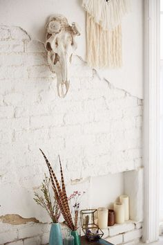 Hanging head against white wall with white yarn weaving next to it.