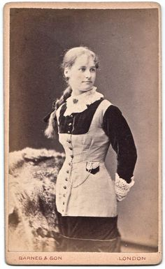 1870s young lady with exterior watch pocket with flap, long chain coming from button hole at waist