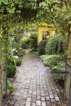 Tuin paadje met kleine stenen, boompjes, verscholen planten, hoekjes Groen geel wit