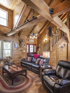 The great room of this Hochstetler Log Homes features a cathedral ceiling and exposed beams for a spacious, open feel! #loghomes #logcabins #exposedbeams