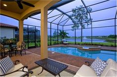 A covered lanai and screened-in pool overlook a water view. The Corciano model by Taylor Morrison. The Mediterra new home community. Naples, FL.