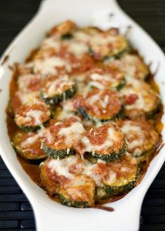 3 large zucchini, sliced into 1/3-inch coins  1 tablespoon extra-virgin olive oil  1/2 cup parmesan cheese, grated and divided in half  1/4 cup Italian bread crumbs  salt & freshly ground pepper to taste  1 cup marinara sauce, homemade or bottled  1/2 cup mozzarella cheese, grated