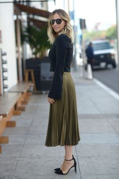 Emily Schuman looks sleek, elegant and ultra feminine in this gorgeous pleated skirt, paired with a bell sleeved crop top and heels for a classy winter style. We love the simplicity of this look! Top: Elizabeth and James, Skirt: Club Monaco, Shoes: Zara.