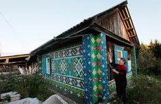 Olga Kostina lives in the rural Russian village of Kamarchaga. For many years, she saved and collected the colorful plastic caps that come on soda bottles. Once Olga amassed several thousand caps, she began her work: decorating her home and surrounding outbuildings with the bits of plastic. How amazing is that!!!
