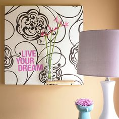 Start by wrapping a canvas with wallpaper and stapling it in place on the back. Print a favorite quote or phrase onto inkjet waterslide decal paper. Cut out words, soak in water for about one minute, peel off backing, and place decal onto canvas.