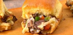 Philly cheesesteak sliders stuffed with steak, cheese, and onions & peppers are a slam-dunk game time appetizer. We'll show you an easy way to make 12 at once!