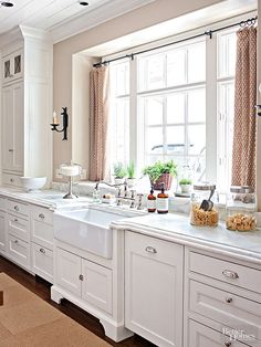 Paired with warm beige wall color and a white plank ceiling, the white cabinets in this cottage kitchen project the impression of patina. A farmhouse sink complements the cabinet design, while a thick countertop with a decorative edge adds elegance to the charming cottage aesthetic.