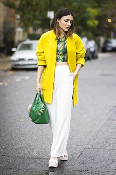 Anisa Sojka wearing yellow Zara oversized coat, green and yellow Baliya Jekkah cropped top, white wide-leg ASOS trousers, green Givenchy Antigona bag, See Me Bags fur pom pom, the little heart and forget me knot Love is rings and white ASOS chunky white sandal heel. Fashion blogger street style shot in London by Cristiana Malcica.