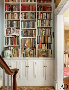 A stair hall landing featuring a built in book case | archdigest.com A bookcase was built into the stair hall outside the study.