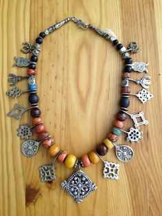 Africa | Necklace from the Berber people of Morocco. An assortment of old and antiques beads and pendants: red and pink coral beads, jet beads, coin silver beads and pendants, copal/'African' amber beads, amazonite and stone beads. | © Jose M. Pery