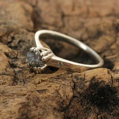 Rough diamond engagement ring with pave set diamonds on the side