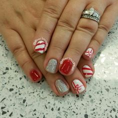 Christmas nails. Candy cane, presents. and a silver glitter nail.