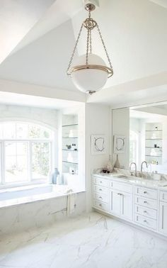 Chic bathroom features a Modern Globe Pendant illuminating a white dual washstand topped with gray and white marble under a full length mirror. Master bathroom boasts a marble clad tub placed under an alcove filled with glass shelves. Marble Bathroom Floor, White Marble Bathrooms, White Master Bathroom, Master Tub, White Marble Kitchen, Gray And White Bathroom, Chic Bathrooms, Dream Bathrooms, Beautiful Bathrooms