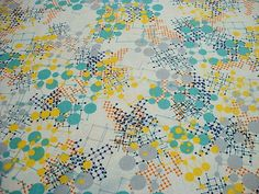 This multi-colored geometric pattern on a white background is part of Moda's Sphere quilting fabric line.