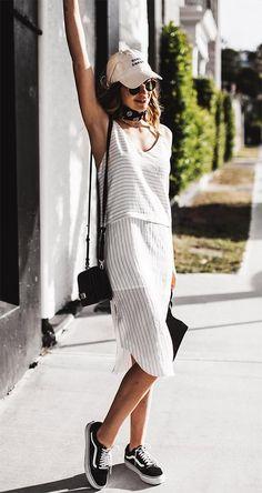 Street style look com vestido listrado e boné.