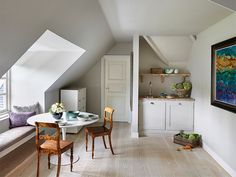 Tucked beneath a sloped roof, this cozy breakfast nook in Surrey, England by Sigmar mixes rustic and modernist furnishings, including a Saarinen-style Tulip table.