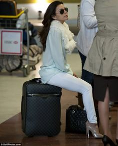 All getting a bit much? Eva rested her feet for a moment by sitting on her Louis Vuitton suitcase