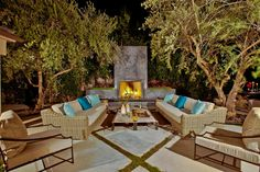 ~ The focal point of this contemporary garden is the outdoor fireplace with built-in planters ~ Upholstered cushions atop wicker sofas provide ample seating, and with a cozy fire as a backdrop, you're sure to spend hours entertaining under the stars ~