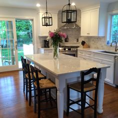 Open concept kitchen and dining room.  White cabinets and LG Viatera Minuet quartz countertops.  Ballard LeMans stool. Lantern pendants.