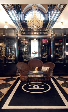 Closet, Champ d'Or Estate, Hickory Creek, Texas - The owner re-created Chanel's Paris boutique in her master closet: it is outfitted with 18K gold doorknobs, a vanity with an antique chair purchased in France, a $30K custom gold chandelier, made in Florence, a custom iron railing modeled after the famed mirrored one in the Chanel store on Rue de Cambon in Paris, and a $10K custom area rug with the brand's intersecting-C logo.