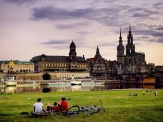 Dresden    Photograph by Berthold Steinhilber, laif/Redux    Bikers rest on the banks of the Elbe across from the cathedral and the royal palace.
