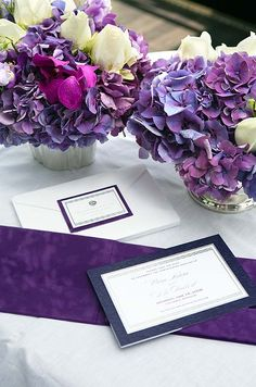 An arrangement of purple hydrangeas and white roses match the hues of this wedding invitation.