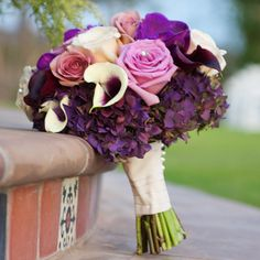 (I love the different shades of purples in this bouquet with some lighter accents. A smaller all white version would be lovely for the girls. So beautiful! My grandmother collects antique buttons and I think it would be beautiful to have some added on the ribbon of a hand tied bouquet.)    Photo Credit: Amanda Marie Photography.
