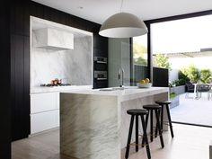 Idea cucina moderna con isola centrale in marmo di Carrara, eleganti sedie e mobili in ebano