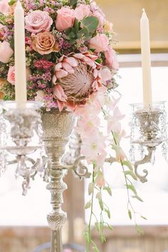 Cascading wedding centerpiece with protea, roses and orchids.