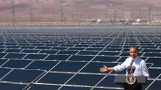President Obama speaks about clean energy with a field of solar panels behind him.
