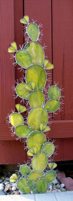 Of my own design this Prickly Pear Cactus makes quite a statement. It truly is picky too! Many wires were soldered into place and carefully bent into shape. The flowers are bright yellow. The glass of the cactus are of varying greens with the slightest streaking of blue. Cactus pieces are soldered onto A 1/2 Inch copper pipe. All are overlaid for a realistic look. The top most cactus is a separate piece and will need to be set into place. This could be used as an indoor decoration by add...