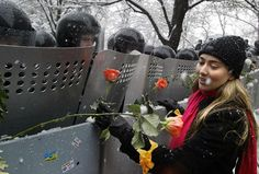 A Ukrainian woman places carnations into shields of anti-riot policemen standing outside the presidential office in Kiev. Ukraine, during the 2004 Orange Revolution. [2004]