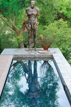 The raised lap pool captures the reflection of another prominent sculpture by Ruhan Janse van Vuuren and a metal branch sculpture by Dahla Hulme. Renowned landscaper De Wet Louw's Pretoria garden.