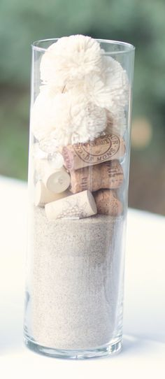 Fill candle glasses with white beach sand and top with champagne/wine corks, shells, and white flowers. A beautiful way to do a centerpiece without water or candles.