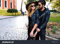 Young pretty couple in love hugs on the street of old town, wearing stylish total black leather rock n roll clothes and sunglasses. Outdoor fashion portrait of lovers.