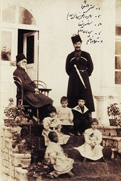 Shams al-Sho'ara (Abdulhossein Mirza Shams Molkara), seated, his son-in-law Amanullah Mirza Jahanbani (1869-1912) standing on the right, small boy wearing a hat (Mansour Mirza Jahanbani), two little girls (Pouran Khanom Jahanbani, Touman Khanom Jahanbani), and an African slave girl, 1900s.