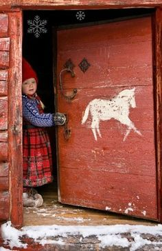 Nordic Winter Norwegian Christmas Elf, traditional norwegian scandinavian winter christmas red plaid dress and shoes with red elf hat. And a painted horse on the door. Norwegian Christmas, Scandinavian Christmas, Scandinavian Cottage, Swedish Cottage, Scandinavian Style, Old Doors, Windows And Doors, Antique Hardware, We Are The World