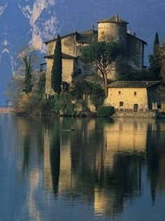Castel Toblino in Trentino-Alto Adige, Northern Italy. Built as an ancient temple, now one of the most renowned lake fortresses in Trentino. Various legends and forbidden love affairs have made it famous. It was Cardinal Bernardo Clesio in the 16th century and later on the nobles of Madruzzo, who made it look the way it does today - all that remains of the medieval layout are a wall to the west and a turret. Over the years the castle has been turned into a hotel with restaurant and cafè now…