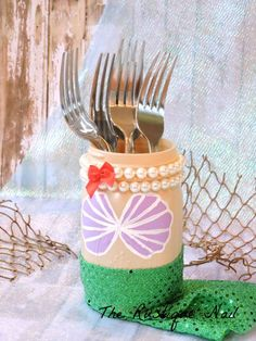 Make this little mermaid inspired DIY. You will need 1 pint size jar (5 1/2 inches tall), paint, green sequin fabric, and pearls or shells.