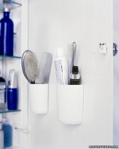 "From MarthaStewart.com: ""Combs, brushes, and toothpaste take up considerable space when laid horizontally on a shelf. Flat-backed, self-adhesive cups on the inside of the cabinet door hold them more efficiently."""