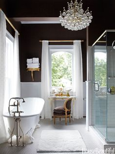 In an antique-filled Victorian house in Illinois, designer Annie Brahler chose the master bath's chocolaty walls to play up the brilliant whites of a recycled tub, curtains in Kally Almost White sheer from Hancock Fabrics, and Daltile floor and shower tiles. The crystal light fixture is a 1980s update of old-school glamour.