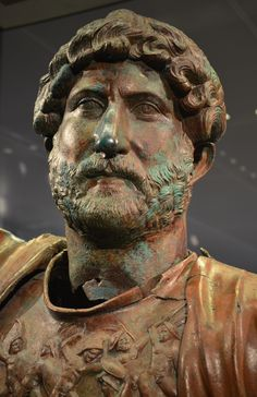ISRAEL~A STATUE of HADRIAN:apparently used for the ritual worship of the emperor,was discovered in a camp of theRoman army.One of the few extant bronze sculptures of an emperor from the Roman Period,it portrays Hadrian in the typical pose of the supreme military commander greeting his troops.His muscle cuirass is decorated w/an enigmatic depiction of archaic warriors.Probably cast in an imperial workshop+features the standardized likeness of the emperor,down to the unique shape of his…