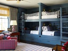 This nautical-inspired bunk room in a Hamptons home by Steven Gambrel features lots of room for storage with built-ins and under-bed drawers. Custom netting provides safety for the top bunks.