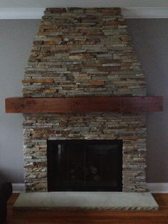 Stone fireplace with wood mantle... Love this look. And love the family who owns it!